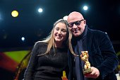 Italian director Gianfranco Rosi poses with his daughter after receiving the Golden Bear for Best Film for the film 'Fuocoammare ' during the awards...