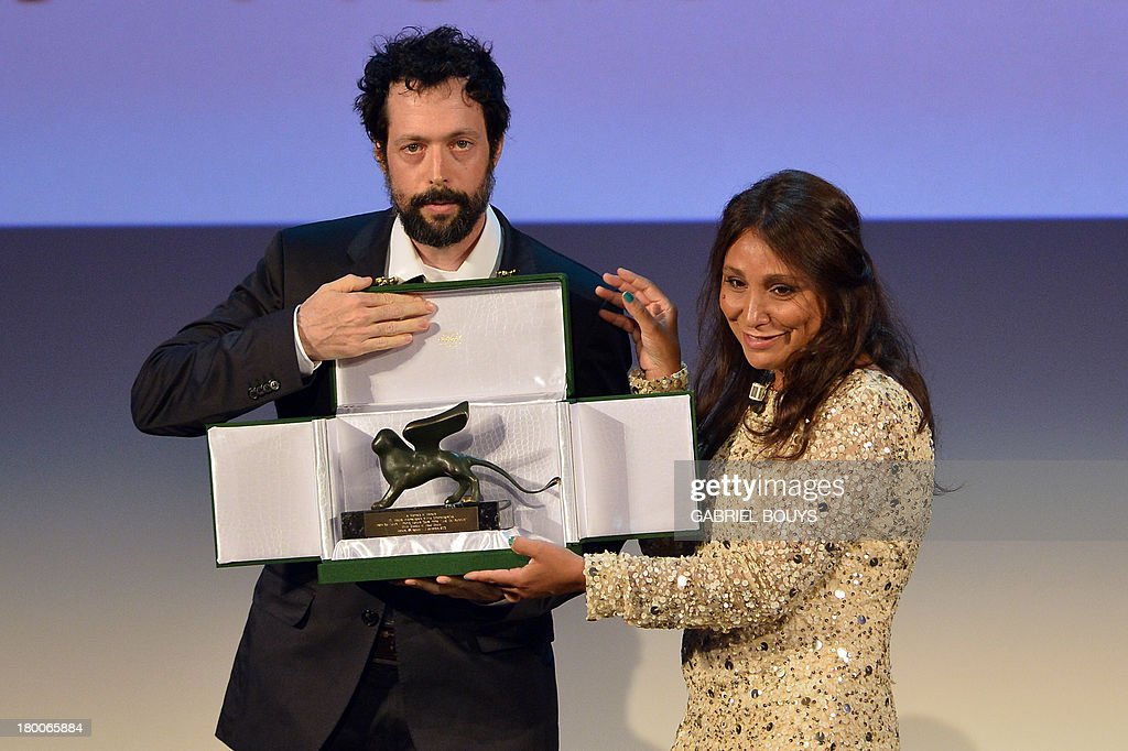 Italian Director Noaz Deshe accepts the Lion of the future - ?Luigi de Laurentiis? Venice award for a debut film from Jury president Haifaa al-Mansour during the award ceremony of the 70th Venice Film Festival on September 7, 2013 at Venice Lido.