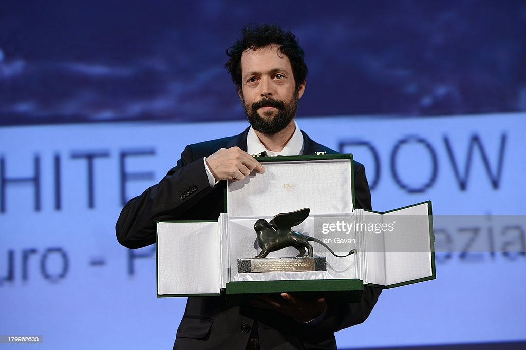 """Italian Director Noaz Deshe poses with his Lion of the future - """"Luigi de Laurentiis"""" Venice award for a debut film on stage during the Closing Ceremony at the 70th Venice International Film Festival at the Palazzo del Casino on September 7, 2013 in Venice, Italy."""