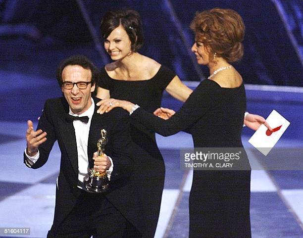 Italian director Roberto Benigni is led off the stage by presenteractress Sophia Loren after winning the Oscar for Foreign Language Film for his...