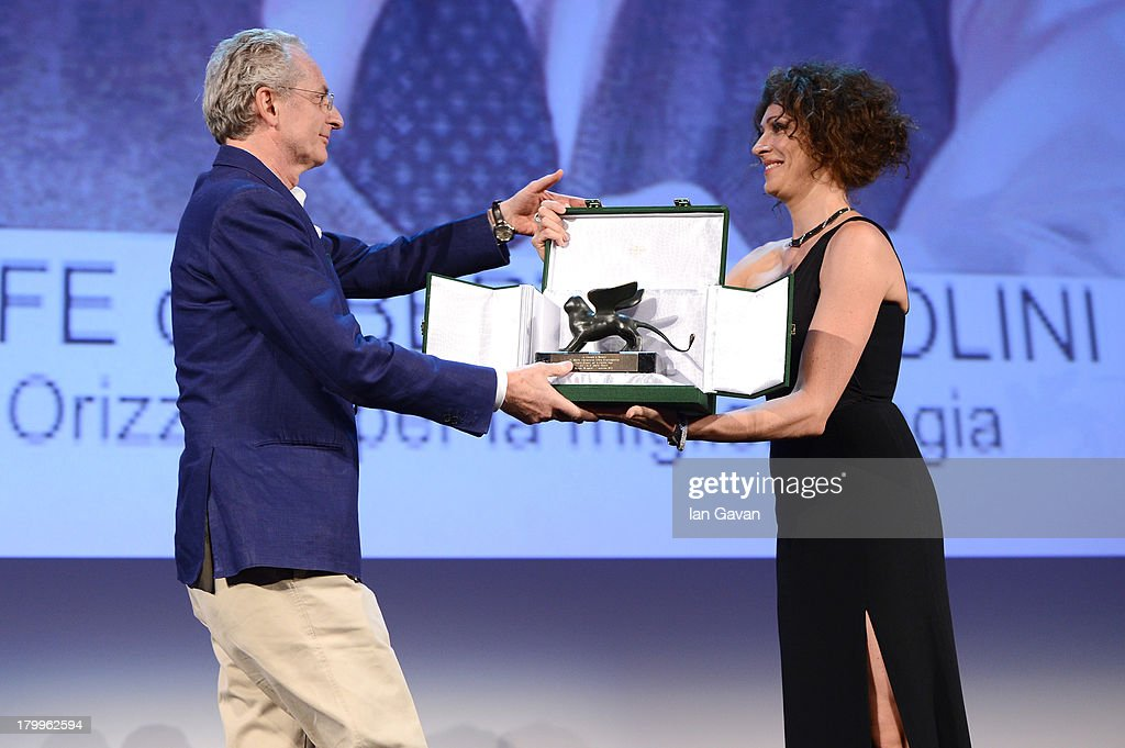 Italian director Uberto Pasolini accepts the Orizzonti award for best director for his movie 'Still Life' from Jury member Ksenia Rappoport on stage during the Closing Ceremony at the 70th Venice International Film Festival at the Palazzo del Casino on September 7, 2013 in Venice, Italy.