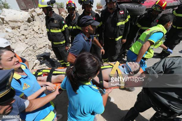 Italian emergency workers evacuate on a stretcher a boy who was was trapped by rubble in Casamicciola Terme on the Italian island of Ischia on August...