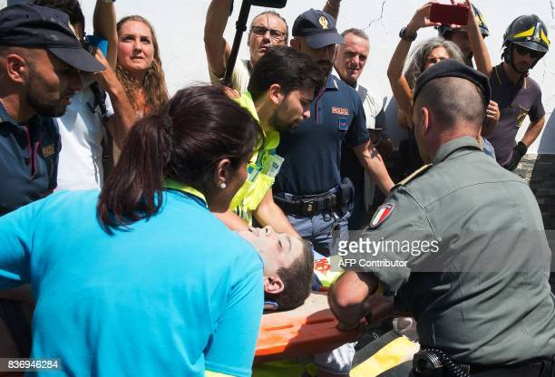 Italian emergency workers evacuate on a stretcher Ciro a 11 yearold boy who was trapped by rubble in Casamicciola Terme on the Italian island of...
