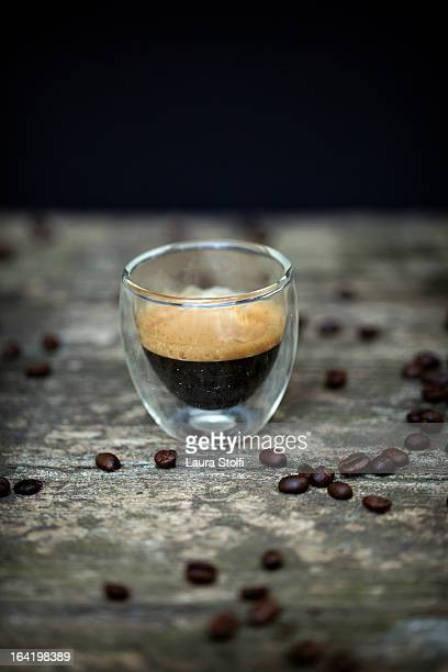 Italian espresso coffee in glass and raw beans