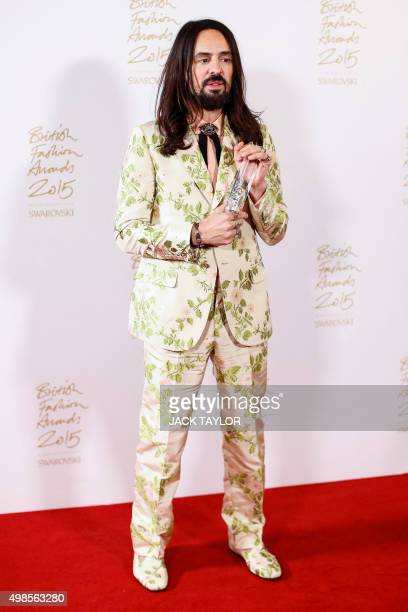 Italian fashion designer Alessandro Michele poses for pictures with his 'International Designer' award during the British Fashion Awards 2015 in...