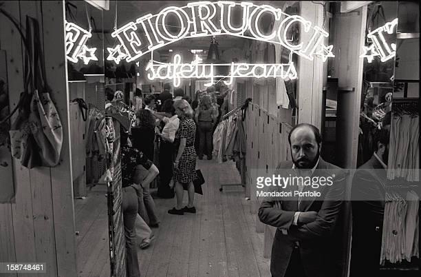 Italian fashion designer and entrepreneur Elio Fiorucci at the entrance of his shop in San Babila square Behind him the neon sign saying Fiorucci...