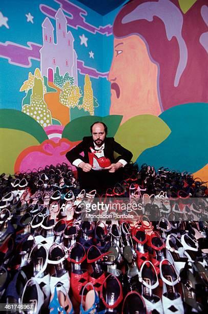 Italian fashion designer and entrepreneur Elio Fiorucci posing beside the last shoes designed by himself Milan 1972