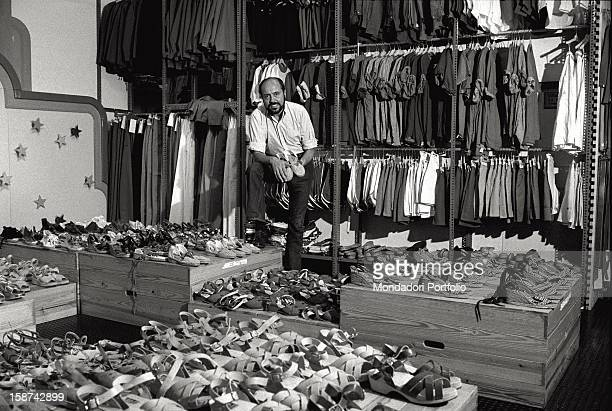 Italian fashion designer and entrepreneur Elio Fiorucci posing in a his shop among the clothes and the shoes to be sold to the retailers Milan 1977
