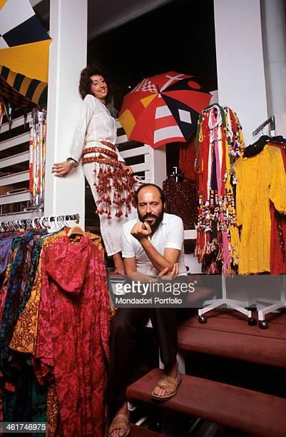 Italian fashion designer and entrepreneur Elio Fiorucci posing in his shop in Galleria Passarella In the background the shop assistant Cristina...