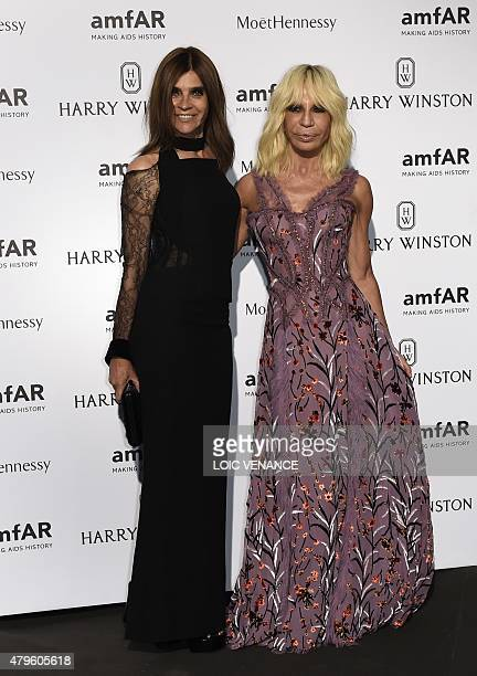 Italian fashion designer Donatella Versace and French stylist Carine Roitfeld pose prior to the Amfar dinner on the sidelines of the Paris fashion...