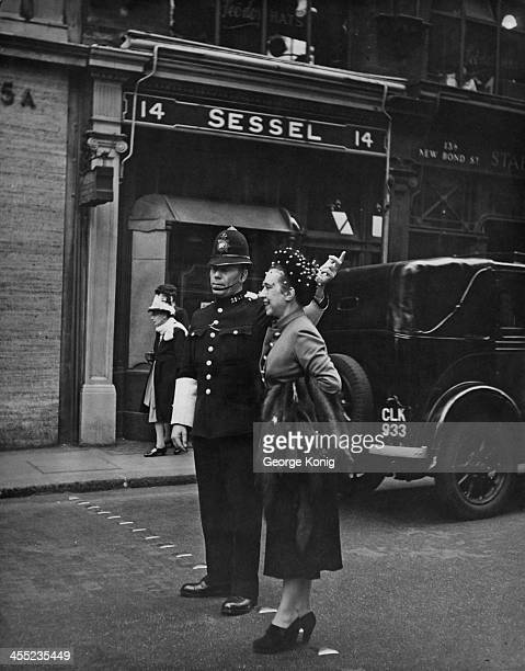 Italian fashion designer Elsa Schiaparelli pauses for a few words with a local police officer on New Bond Street London 8th October 1947