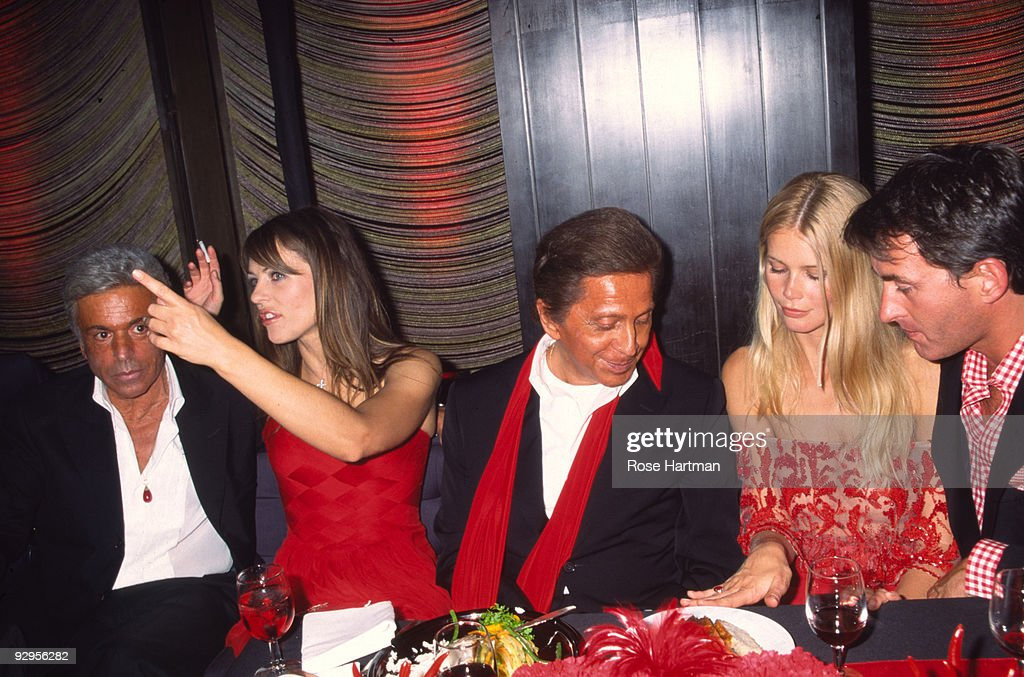 Italian fashion designer Valentino sits at a table with from left his business partner Giancarlo Giammetti British actress and model Elizabeth Hurley...