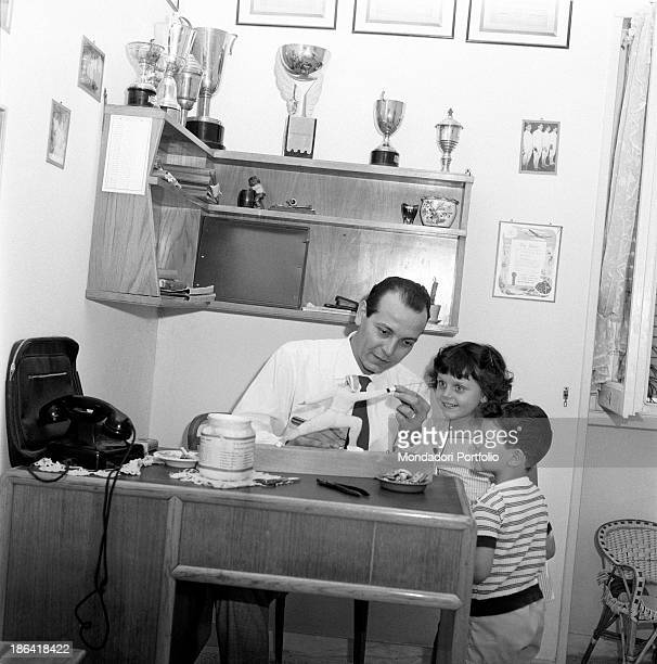 Italian fencer Roberto Ferrari sitting in his flat in Via Vallescrivia 14 showing the scale model of a fencer to his children Marzia and Andrea Rome...