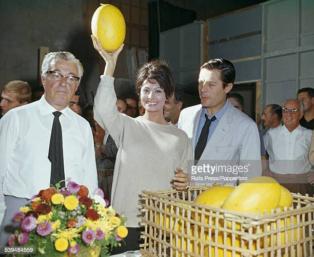 Italian film actress Sophia Loren holds a melon up in the air with on left film director and actor Vittoria De Sica and on right actor Marcello...