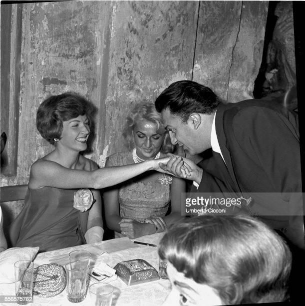 Italian film director Federico Fellini kisses the hand of actress Carla Del Poggio Carla del Poggio is with Anna Salvatore