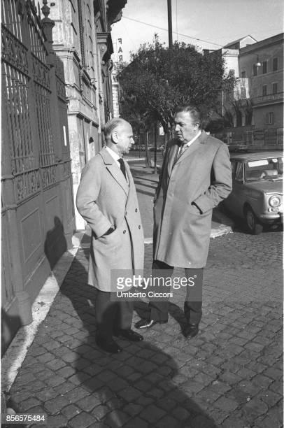 Italian film director Federico Fellini talks to a friend in the street Rome 1970