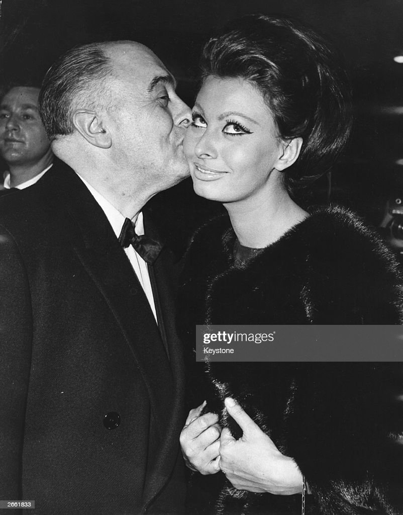 Italian film producer Carlo Ponti kisses his wife, actress <a gi-track='captionPersonalityLinkClicked' href=/galleries/search?phrase=Sophia+Loren&family=editorial&specificpeople=94097 ng-click='$event.stopPropagation()'>Sophia Loren</a> after she received the first Alexander Korda award, naming her 'International Star of the Year', at the world premiere of her new film 'Lady L' at The Empire, Leicester square.