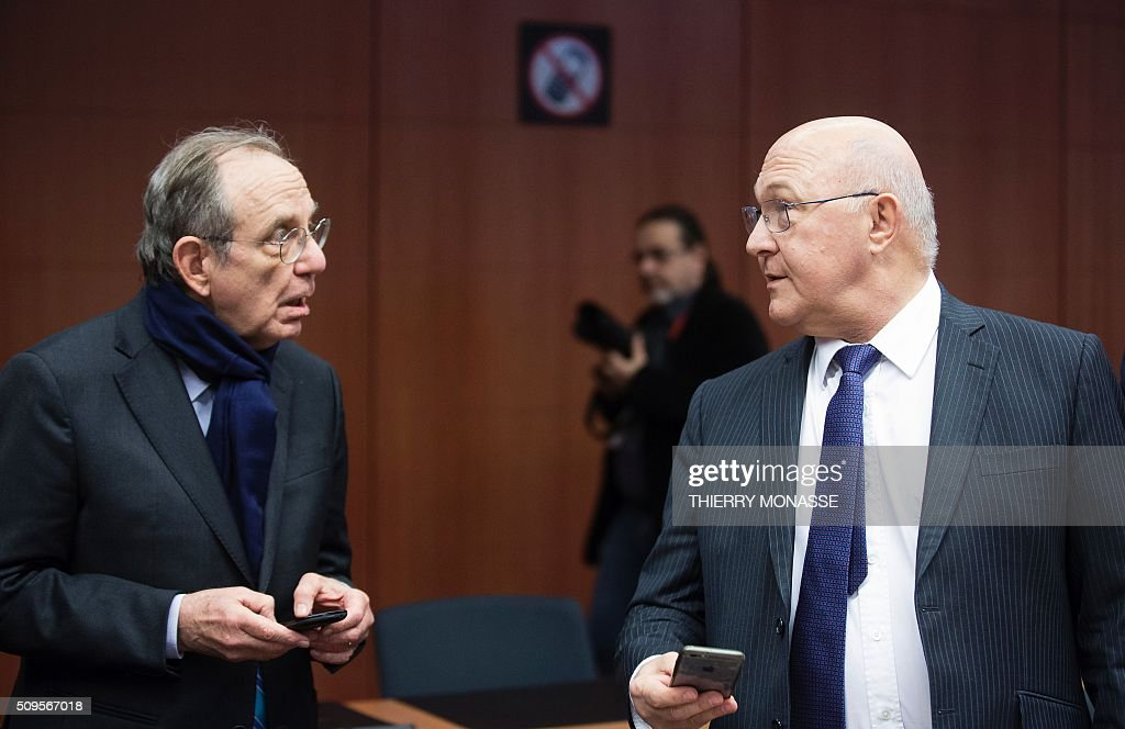 Italian Finance Minister Pier Carlo Padoan (L) and French Finance and Public Accounts Minister Michel Sapin (R) look on their telephones while a 'no telephone' sign is seen in the background prior to a meeting of Eurogroup ministers at the European Council headquarters in Brussels on February 11, 2016. / AFP / THIERRY MONASSE