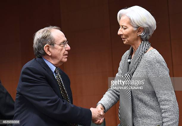 Italian Finance Minister Pier Carlo Padoan and International Monetary Fund Managing Director Christine Lagarde shake hands during an emergency...