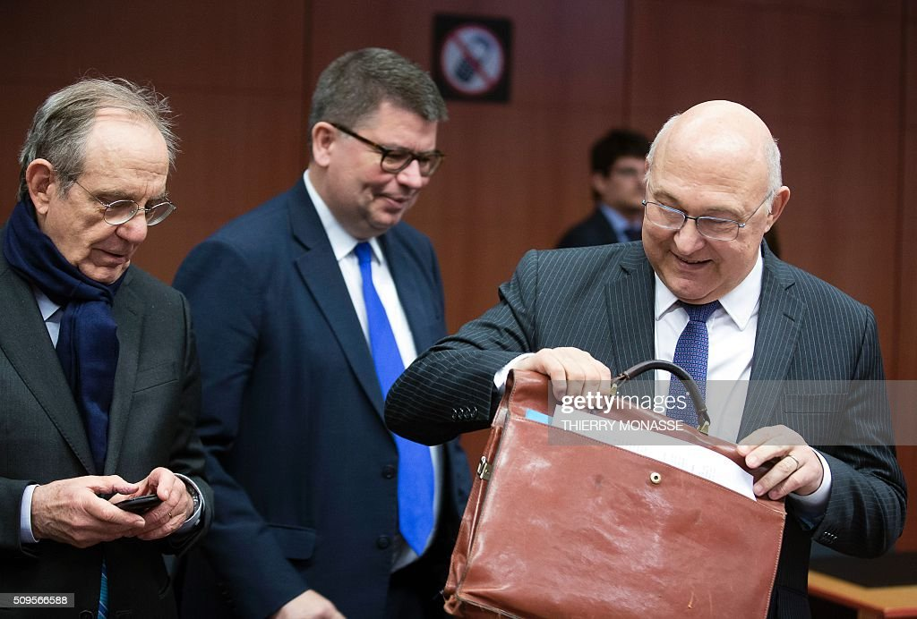 Italian Finance Minister Pier Carlo Padoan (L) talks with French Finance and Public Accounts Minister Michel Sapin (R) prior to a meeting of Eurogroup ministers at the European Council headquarters in Brussels on February 11, 2016. / AFP / THIERRY MONASSE