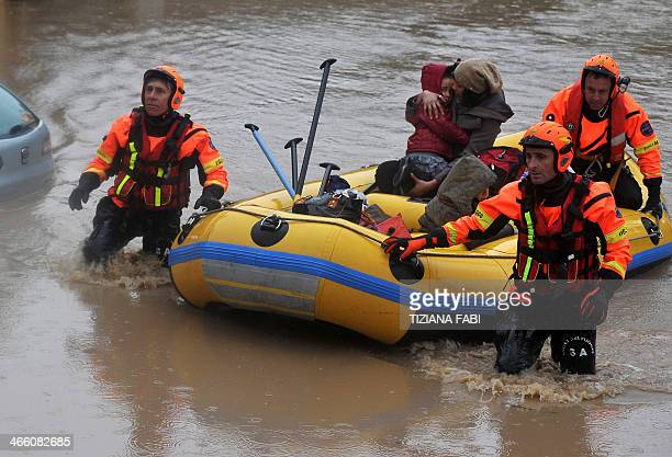 Italian firefighters rescue people in a flooded street in Prima Porta in the outskirts of Rome on January 31 2014 after torrential rains hit the...