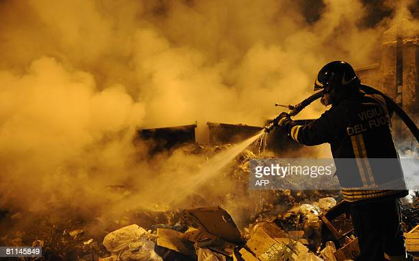 Italian firefighters tries to extinguish burnt uncollected rubbish in a street of the center of Naples on May 19 2008 Residents of Naples fed up with...