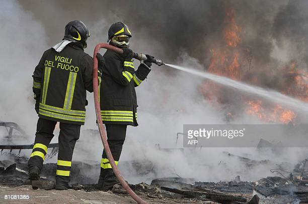 Italian firefighters try to extinguish a fire at a Roma camp on May 14 2008 in the Ponticelli neighborhood of Naples The camp was set on fire by an...
