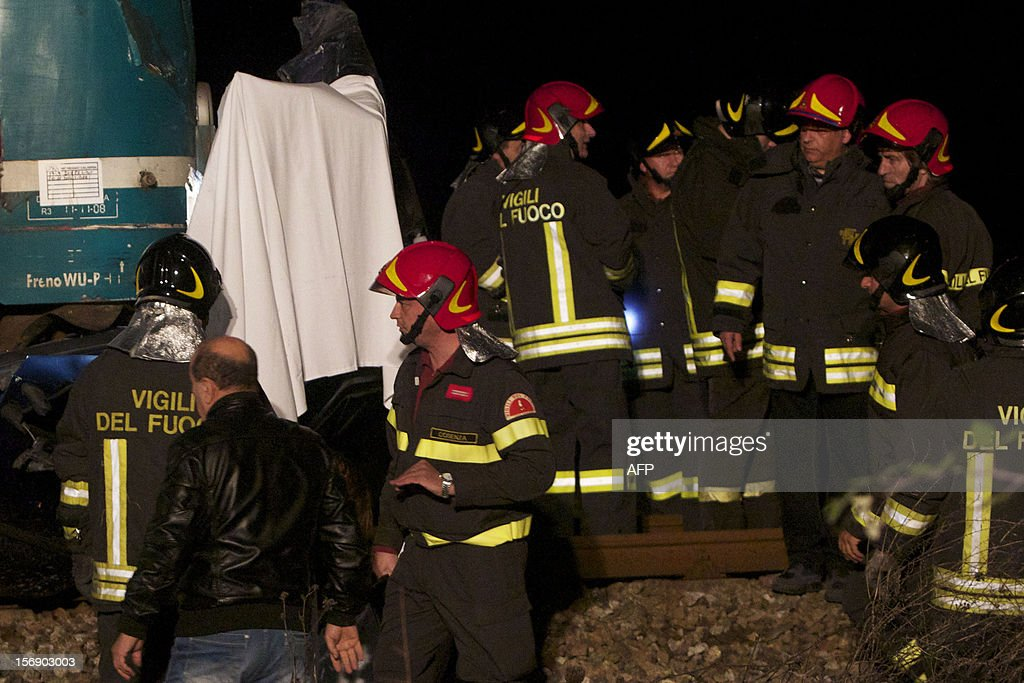 Italian firefighters work at the site of an accident where a train collided with a car full of Romanian workers, in Rossano, on November 24, 2012. Six Romanian workers who were involved in the seasonal picking of clementines were killed when the train struck their car at a crossing. AFP PHOTO / MARIO TOSTI