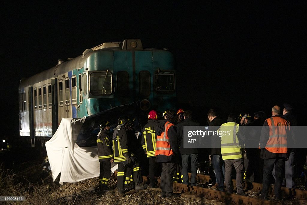 Italian firefighters work at the site of an accident where a train collided with a car full of Romanian workers, in Rossano, on November 24, 2012. Six Romanian workers who were involved in the seasonal picking of clementines were killed when the train struck their car at a crossing.