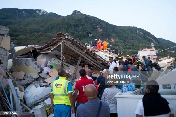 TOPSHOT Italian firemen and emergency workers search through rubble of a collapsed house in Ischia on August 22 after an earthquake hit the popular...