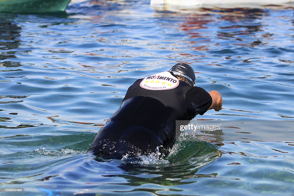 Italian Five Star Movement political leader Beppe Grillo takes the start to swim across the Strait of Messina in an election campaign stunt and in protest against plans for a bridge from the Italian mainland to Sicily on October 10, 2012 in Cannitello, in the Italian region of Calabria. The populist leader, which campaigns on a variety of environmental and anti-corruption issues, is taking part in local elections in Sicily scheduled for October 28 to elect a new regional governor and assembly.