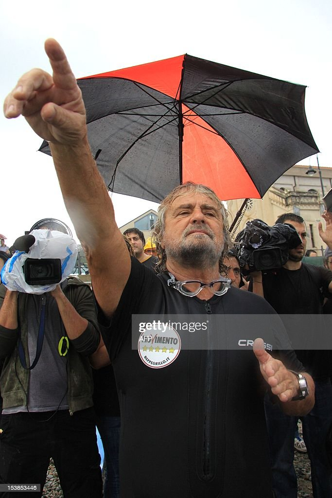Italian Five Star Movement political leader Beppe Grillo waves to supporters before swimming across the Strait of Messina in an election campaign stunt and in protest against plans for a bridge from the Italian mainland to Sicily on October 10, 2012 in Cannitello, in the Italian region of Calabria. The populist leader, which campaigns on a variety of environmental and anti-corruption issues, is taking part in local elections in Sicily scheduled for October 28 to elect a new regional governor and assembly. AFP PHOTO / ALBANO ANGILETTA