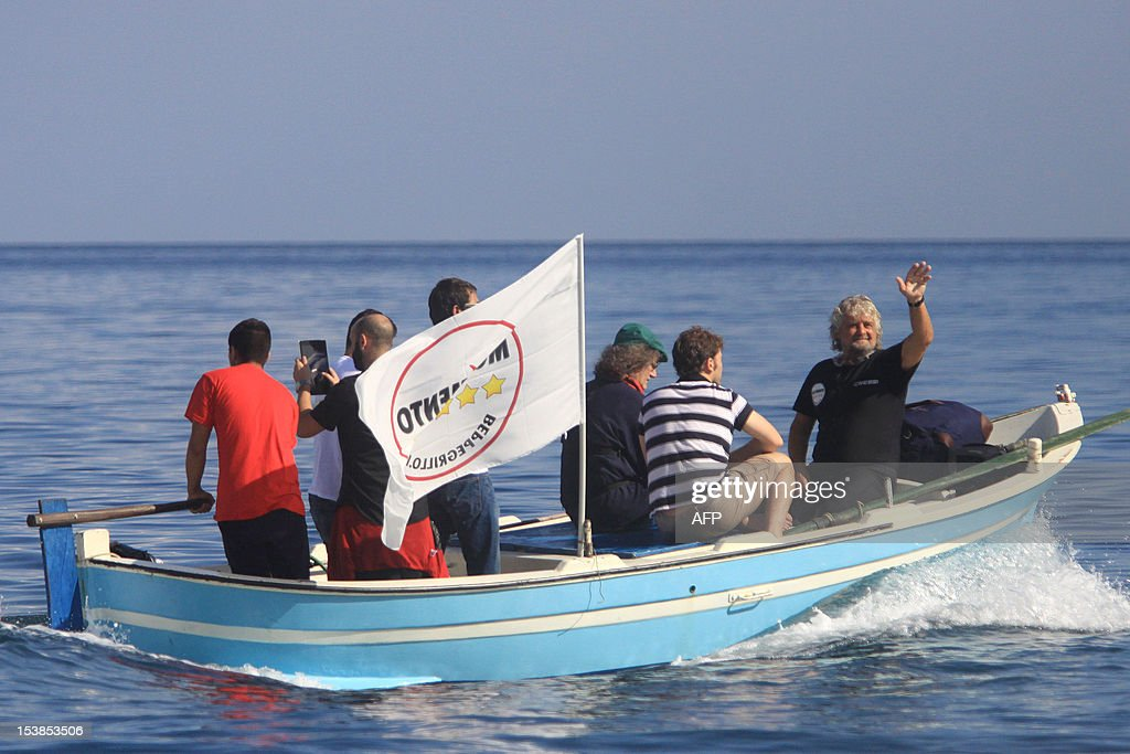 Italian Five Star Movement political leader Beppe Grillo (R) waves to supporteres before swimming across the Strait of Messina in an election campaign stunt and in protest against plans for a bridge from the Italian mainland to Sicily on October 10, 2012 in Cannitello, in the Italian region of Calabria. The populist leader, which campaigns on a variety of environmental and anti-corruption issues, is taking part in local elections in Sicily scheduled for October 28 to elect a new regional governor and assembly.