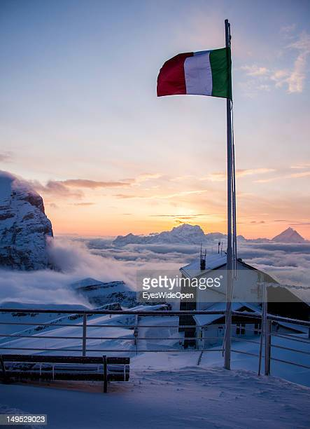 Italian flagg and panoramic view at sunrise of the Dolomite Alps from the alpine mountain hut Rifugio Lagazuoi on March 9 2012 in Cortina D'Ampezzo...