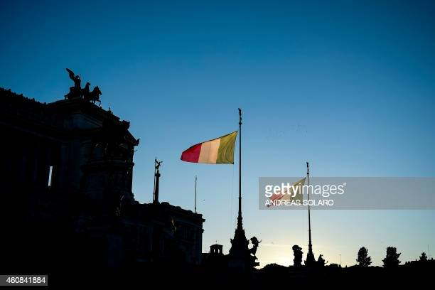 Italian flags wave at the 'Altare della Patria' at sunset in Rome on December 26 2014 AFP PHOTO / ANDREAS SOLARO