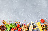 Italian food background with vine tomatoes, basil, spaghetti, olives, parmesan, olive oil, garlic Ingredients on stone table Copy space Top view