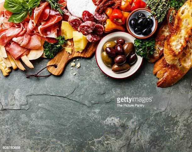 Italian food ingredients background with ham, salami, parmesan, olives, bread sticks on stone slate