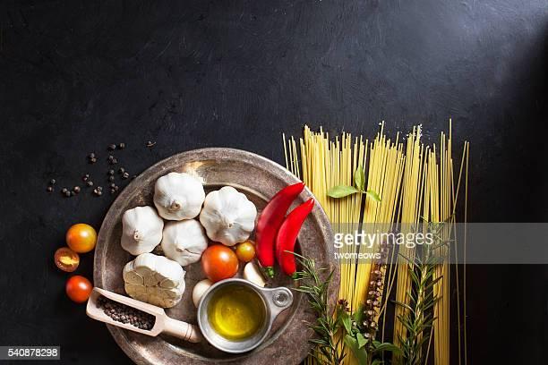 Italian food, spaghetti recipe ingredient on black texture background.