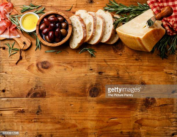 Italian food with Ham, Sliced bread Ciabatta, Parmesan and Olives on wooden background copy space