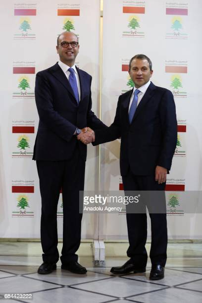 Italian Foreign Minister Angelino Alfano and Lebanese Foreign Minister Gebran Bassil shake hands as they pose for photo after their press conference...
