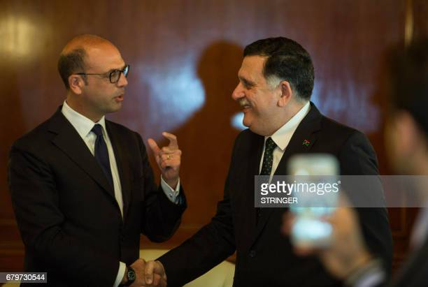 Italian Foreign Minister Angelino Alfano shakes hands with the head of Libya's Government of National Accords Fayez alSarraj during a meeting on May...