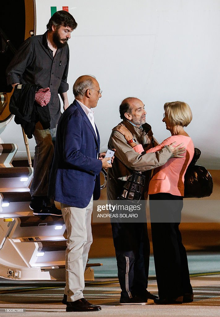 Italian Foreign minister Emma Bonino (R) greets Italian journalist Domenico Quirico (C) and Belgian national Pierre Piccinin (L), both kidnapped in Syria in early April, as they disembark from the airplane on September 9, 2013 at Ciampino military airport in Rome. AFP PHOTO / ANDREAS SOLARO