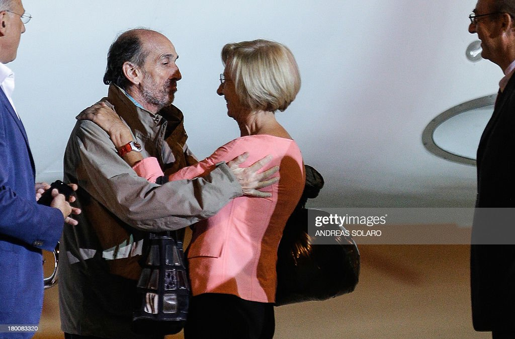 Italian Foreign minister Emma Bonino (C) greets italian journalist Domenico Quirico and Belgian national Pierre Piccinin (unseen), both kidnapped in Syria in early April, as they disembark from the airplane on September 9, 2013 at Ciampino military airport in Rome.