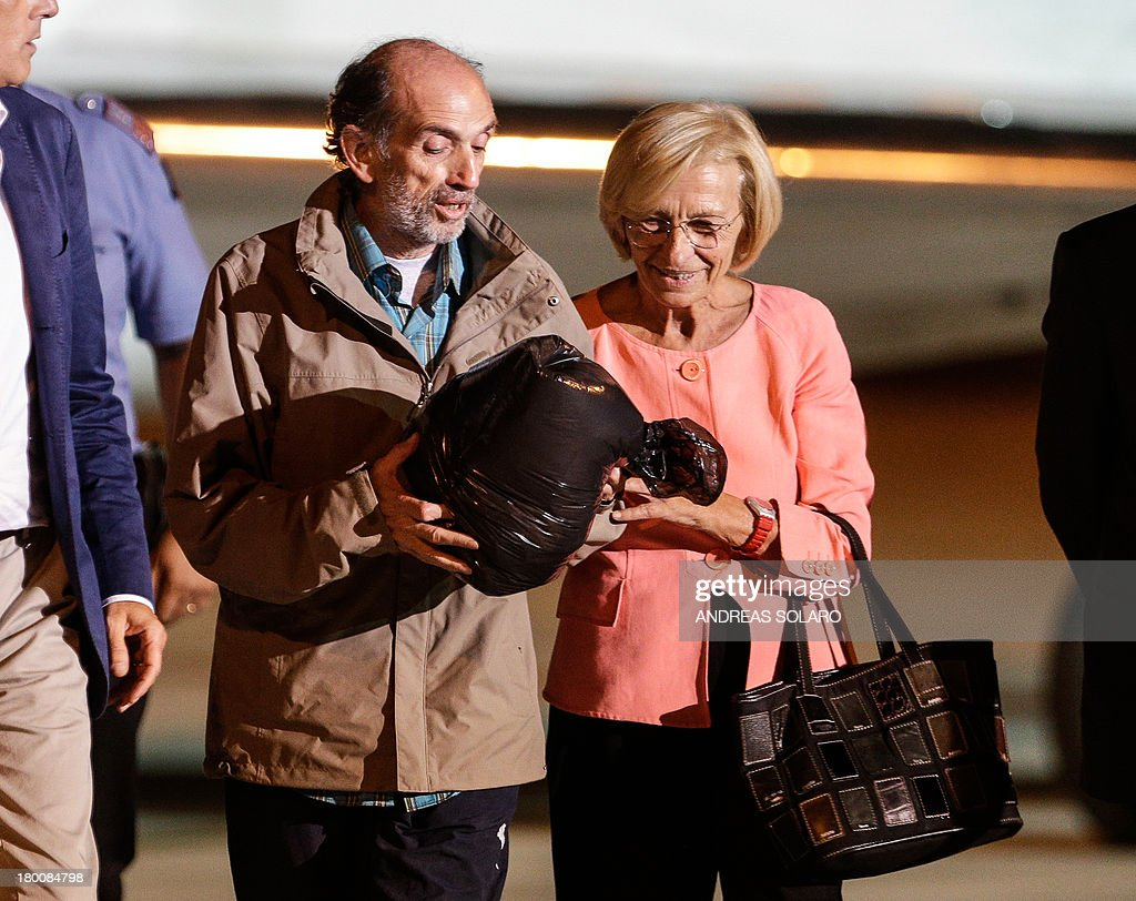 Italian Foreign minister Emma Bonino (R) greets Italian journalist Domenico Quirico and Belgian national Pierre Piccinin (unseen), both kidnapped in Syria in early April, as they disembark from the airplane on September 9, 2013 at Ciampino military airport in Rome.