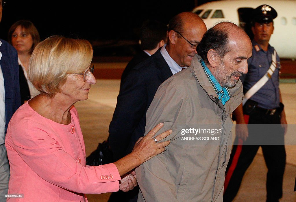 Italian Foreign Minister Emma Bonino (L) greets Italian journalist Domenico Quirico who was kidnapped in Syria in early April, after his disembark from the airplane on September 9, 2013 at Ciampino military airport in Rome. AFP PHOTO / ANDREAS SOLARO
