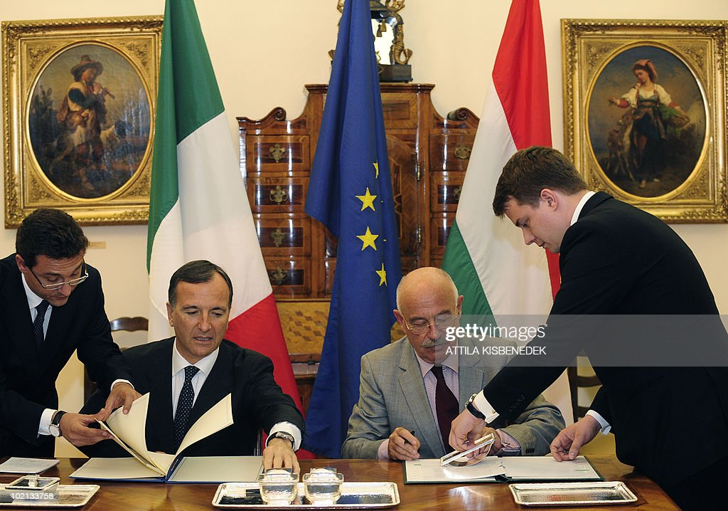 Italian Foreign Minister Franco Frattini (2-L) signs a cooperation aggreement between their countries with his Hungarian counterpart Janos Martonyi (2-R) at the ministry of Foreign Affairs in Budapest on June 16, 2010. Frattini is on a one-day official visit to Hungary.