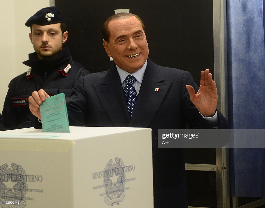 Italian former Prime Minister Silvio Berlusconi casts his ballot at a polling station on February 24, 2013 in Milan. Italians fed up with austerity went to the polls on Sunday in elections where the centre-left is the favourite, as Europe held its breath for signs of fresh instability in the eurozone's third economy. AFP PHOTO / OLIVIER MORIN