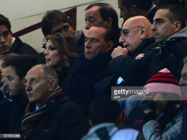 Italian former prime minister Silvio Berlusconi takes place with AC Milan's sporting director Adriano Galliani before the Champions league match...