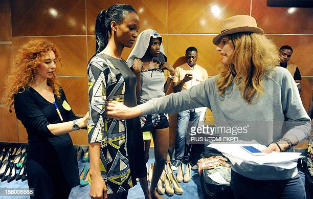 Italian founder of Nigerian based Kinabuti fashion label Caterina Bortolussi assisted by her head of production Francesca Rosset dresses a model for...