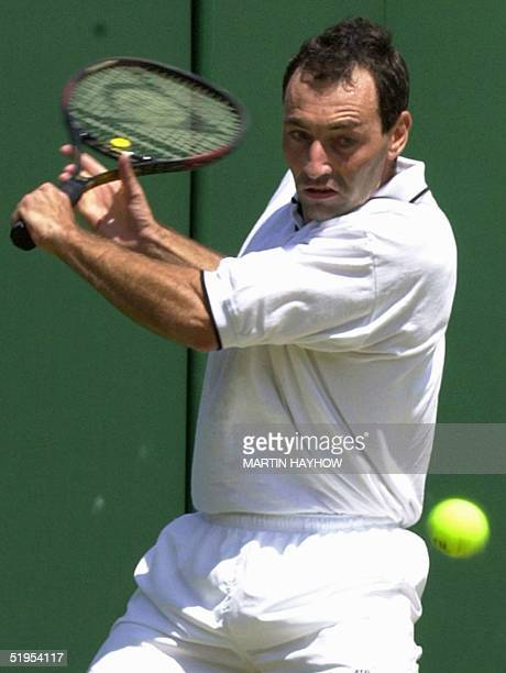 Italian Gianluca Pozzi eyes the ball before returning a backhand slice during his fourthround match at the Wimbledon championships against Zimbabwean...